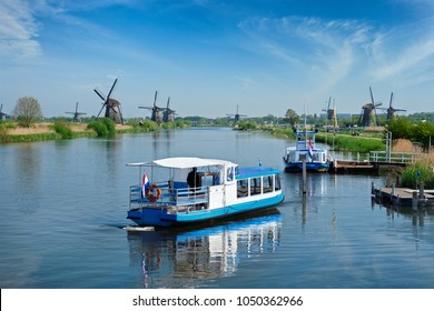 Netherlands rural lanscape with tourist boat and windmills at famous tourist site Kinderdijk in Holland