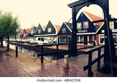 NETHERLANDS. VOLENDAM - JUNE 23, 2015: An ancient wooden bridge across a canal in an ancient city street. Volendam is an ancient fishing village.