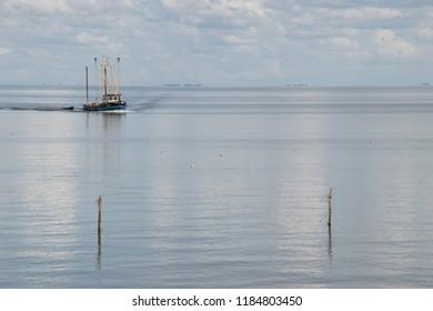 Netherlands,Friesland,Afsluitdijk, july 2018:Fishing boat is emptying the nets, placed along the Aflsluitdijk in a calm peacfull IJsslemeer