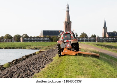 Netherlands,North-Holland,Medemblik,july 2018:lawn mower is mowiing the grass on the Zuiderdijk