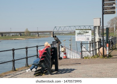 Netherlands,Overijssel,Deventer,april 2019:Woman sitting at IJssel boulevard in Deventer