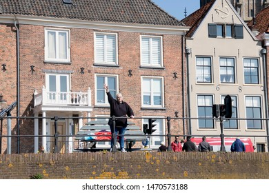 Netherlands,Overijssel,Deventer,april 2019:Woman waving atIJssel boulevard in Deventer
