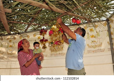 NETIVOT - OCTOBER 02: Israeli Jewish family decorates their Sukkah on the eve of the Jewish holiday Sukkoth on October 02, 2009 in Netivot, Israel.