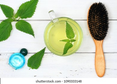 Nettle and healing of lost hair. Alternative livestyle concept,  nettle infusion  with fresh nettle leaves, hair brush and shampoo on white wooden board.