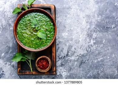 Nettle soup in bowl on wooden surface.Green nettle soup