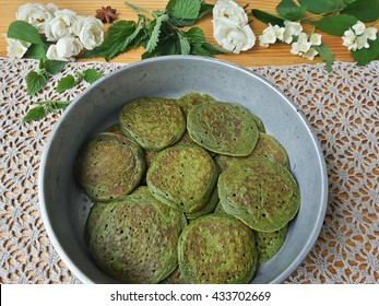 Nettles green pancakes with rose petals, cooking organic food with weed