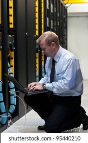 Network administrator is setting up network switches, firewalls and routers using a laptop.