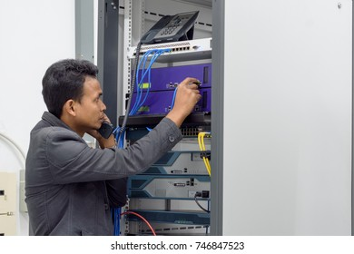 Network administrator talking on the ip phone and connecting utp cable to the network in   datacenter room