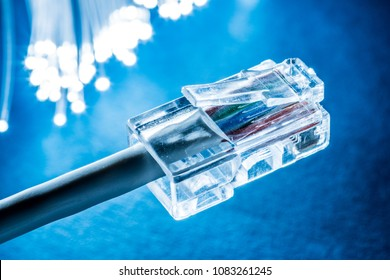 Network cables and optical fibers with lights in the ends. Blue background.