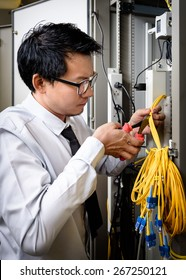 Network engineer cutting fiber optic cable