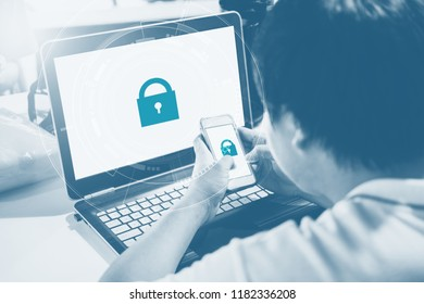 Network and internet devices security system. a man using mobile phone and computer laptop with lock icon technology on screen