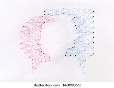 Network of pins and threads in the shape of a man and a woman inside two speech bubbles symbolising an intimate connection and the importance of communication in a relationship.