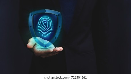 Network Security System Concept, Fingerprint inside a Shield Guard to Protected Identify of User or Personal Information, Present over Businessman Hand, Dark light and Modern Transparent style