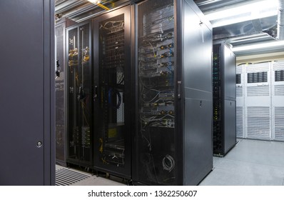 Network server room with parallel rows of mainframe. Corridor in big working data center full of rack servers and supercomputers.