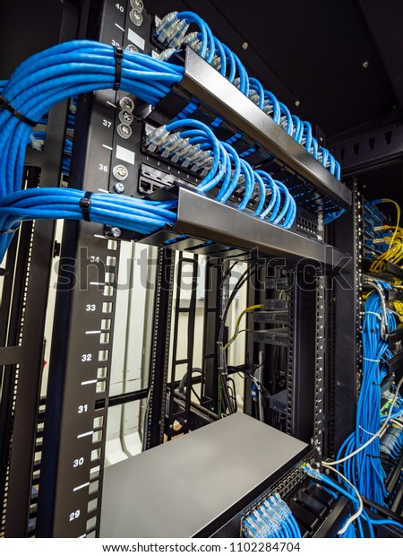 network switch hub and ethernet cables connected in rack cabinet