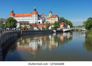 NEUBURG AN DER DONAU, GERMANY - MAY 18, 2017: Neuburg Castle, a residence of Dukes of Palatinate-Neuburg, reflected in Danube in sunny day. The Renaissance castle was built in 1530-1545.