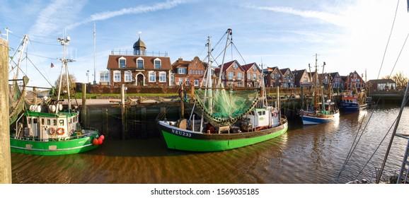 Neuharlingersiel, Germany - November 24, 2016: Fishing boats moored in the harbor at low tide
