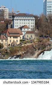 """Neuhausen, Schaffhausen, Switzerland - 03/24/2019: the Rhine Falls with the headquarter of """"SIG Combibloc"""" in the background"""