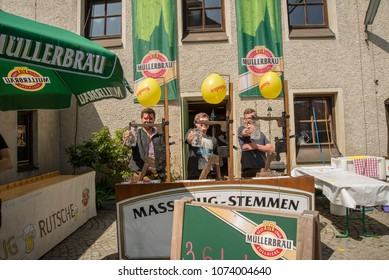 Neuoetting,Germany-April 21,2018:Three young men smile while trying not to puncture the balloons above if they lower their beer mugs