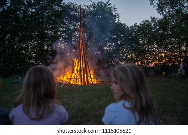 Neuoetting,Germany-June 15,2018: Two girls look at the bonfire burning during the summer solstice feast