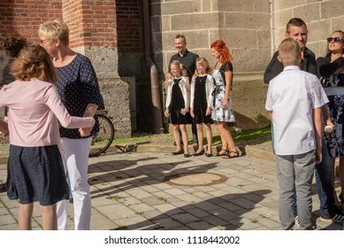 Neuoetting,Germany-June 22,2018: Families pose for pictures with their children outside the local church before Confirmation