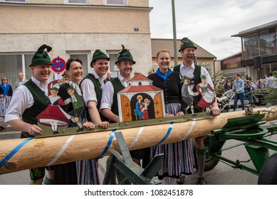 Neuoetting,Germany-May 01,2018: Members of the  traditional folklore group pose behind their guild sign by the maypole installation