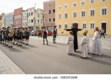 Neuoetting,Germany-May 1,2018The parish priest and altar boys and girls prepare to waylay the parade in order to negotiate a ransom before allowing them to continue their way .