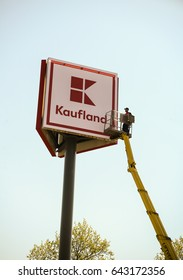 Neuoetting,Germany-May 19,2017: A worker stands on a lilfting platform cleaining a Kaufland supermarket sign