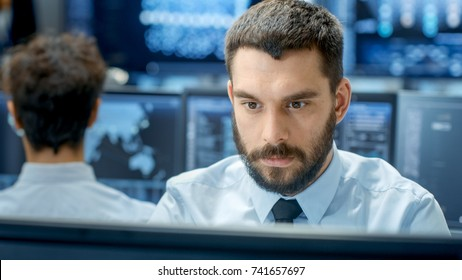 Neural Network and Machine Learning Engineer Programming at His Workstation. Office is Crowded With People Working. Multiple Displays Show Neural Network, Artificial Intelligence Representation.