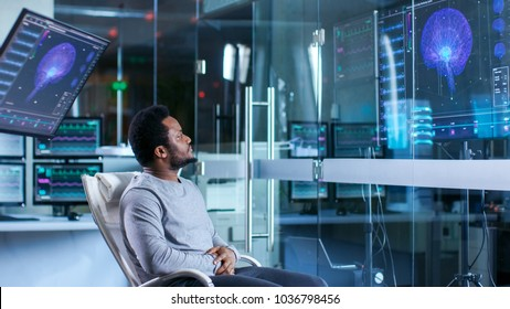 In Neurological Laboratory Man in a Chair Looks at Brain Scan Representation and Health Infographics Shown on Monitors.