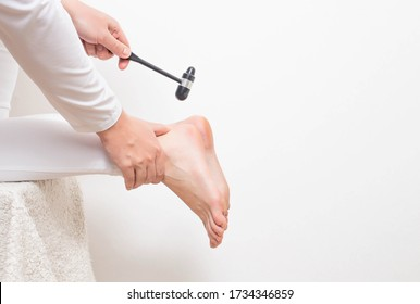 A neurologist doctor checks the Achilles reflex with a neurological hammer. Checking the tibial nerve and the presence of an intervertebral hernia of the spine, copy space