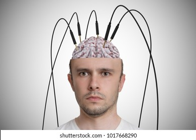Neuroscience and brain research concept. Young man has cables and electrodes in his brain.