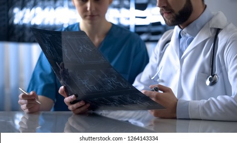 Neurosurgeon and anesthetist discussing cerebral vessels x-ray before operation