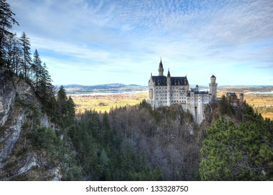 Neuschwanstein Castle. Neuschwanstein Castle is a 19th-century Romanesque Revival palace on a rugged hill above the village of Hohenschwangau near Fuessen (F�¼ssen) in Bavaria, Germany.