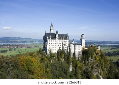 Neuschwanstein castle in autumn on a clear sunny day with lake and city visible, Bavaria Germany