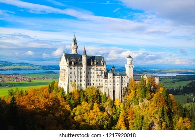 Neuschwanstein castle in Germany, Bavaria, Europe. Autumn landscape of Neuschwanstein with colorful trees, Traveling concept background.