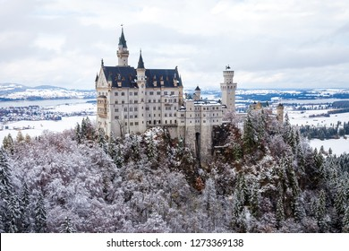 Neuschwanstein Castle (Schloss Neuschwanstein) one day after a snowfall, with the mountains and trees capped with snow