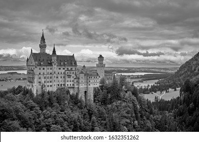 Neuschwanstein castle surrounded by beautiful nature of the Bavarian Alps and a dramatic sky in black and white. Famous tourist landmark and travel destination