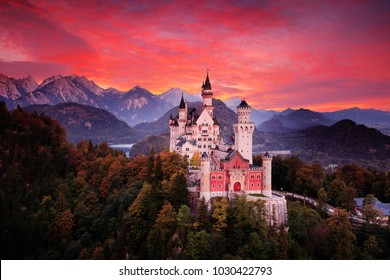 Neuschwanstein fairy tale castle. Beautiful sunset view of the bloody clouds with autumn colours in trees, twilight night, Bavarian Alps, Bavaria, Germany.