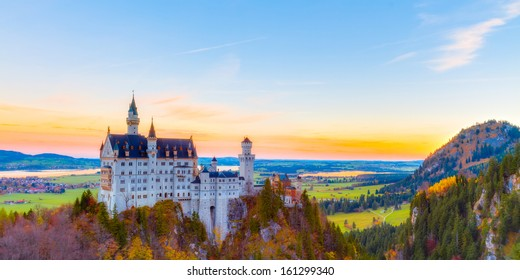Neuschwanstein, Lovely Autumn Landscape Panorama Picture of the fairy tale castle near Munich in Bavaria, Germany with colorful trees in the morning hours