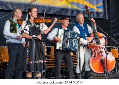Neustadt in Holstein, Germany - August 03, 2019, European Folklore Festival, Karpaty, folk dancers from Bratislava Slovakia. colorful dressed, traditional musicians accompany folk dances on stage