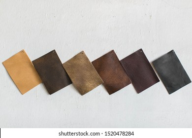 neutral brown and black leather cowhide swatches on white wall, copy space