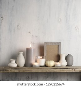 Neutral colored vases, burned candles and frame on rustic wooden shelf against shabby white wall. Home decor.