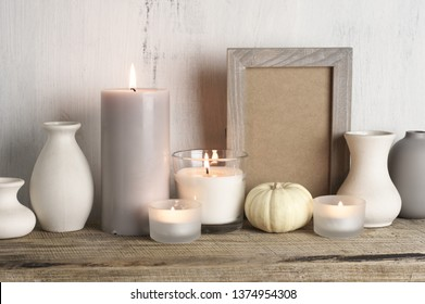 Neutral colored vases, burned candles and empty frame on rustic wooden shelf against shabby white wall. Home decor.