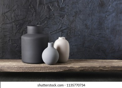 Neutral colored vases on distressed wooden shelf against rough plaster black wall. Home decor.