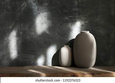 Neutral colored vases on distressed wooden shelf against rough plaster dark grey wall in sunlight. Home decor.