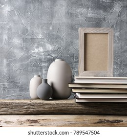 Neutral colored vases, shabby photoframe and stack of books on distressed wooden shelf against rough plaster grey wall. Home decor.