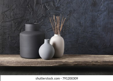Neutral colored vases with wood sticks on distressed wooden shelf against rough plaster black wall. Home decor.