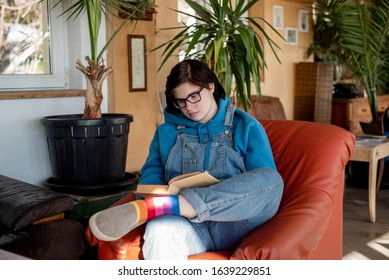 Neutral gender teenager sitting in an armchair and reading a book