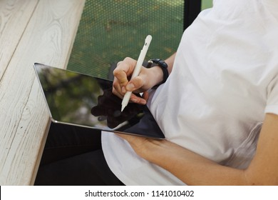 Neutral person with tablet and pen sitting at a cafe